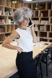 Femme d'affaires supérieure faisant l'appel téléphonique dans un lieu de réunion photos stock
