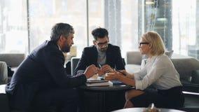 Femme d'affaires supérieure faisant la proposition d'affaires aux associés dans faire des gestes parlant de café banque de vidéos