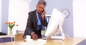Femme d'affaires supérieure parlant au téléphone et travaillant dans le bureau Images libres de droits