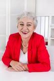 Femme d'affaires supérieure plus âgée attirante s'asseyant au bureau portant au sujet de Photographie stock