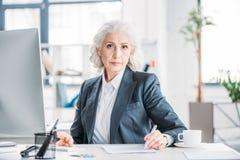 Femme d'affaires supérieure s'asseyant sur le lieu de travail et écrivant avec le stylo Images libres de droits