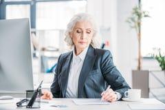Femme d'affaires supérieure s'asseyant sur le lieu de travail et écrivant avec le stylo Photo libre de droits