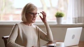 Femme d'affaires supérieure soumise à une contrainte contrariée avec la défaillance coincée d'ordinateur portable ou de système banque de vidéos