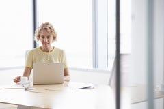 Femme d'affaires supérieure Working On Laptop au Tableau de salle de réunion Photographie stock