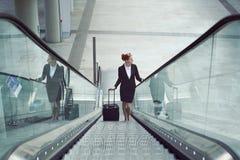 Femme d'affaires sur l'escalator avec le bagage de main Image libre de droits
