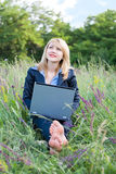 Femme d'affaires sur l'herbe avec l'ordinateur portatif photographie stock libre de droits