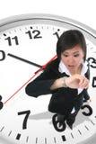 Femme d'affaires sur l'horloge Images stock