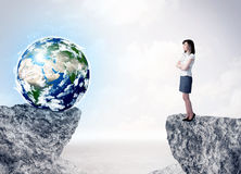 Femme d'affaires sur la montagne de roche avec un globe Photos stock