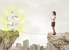 Femme d'affaires sur la montagne de roche avec une marque du dollar Image libre de droits