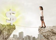 Femme d'affaires sur la montagne de roche avec une marque du dollar Photo stock