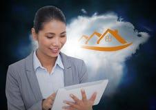 Femme d'affaires sur le comprimé devant le nuage avec le graphique orange de maison Photos stock
