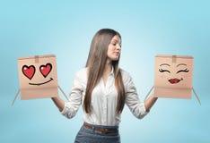 Femme d'affaires sur le fond bleu-clair tenant deux boîtes de carton avec de beaux visages tirés dans des ses mains Photos libres de droits