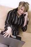 Femme d'affaires sur le téléphone et l'ordinateur portatif Image stock
