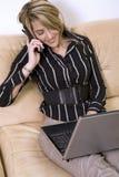 Femme d'affaires sur le téléphone et l'ordinateur portatif images stock