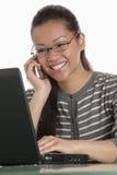 Femme d'affaires sur le téléphone portable et l'ordinateur portatif Images stock