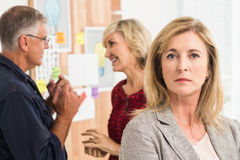 Femme d'affaires sévère en avant avec son équipe derrière Image stock