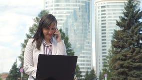 Femme d'affaires Talking au t?l?phone tandis qu'utilisant l'ordinateur portable banque de vidéos
