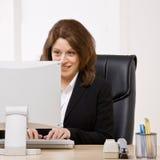Femme d'affaires tapant sur l'ordinateur au bureau photos libres de droits
