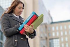Femme d'affaires tenant des dossiers avec des documents dehors Photo libre de droits