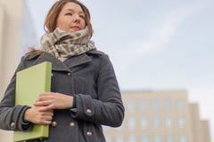 Femme d'affaires tenant des dossiers avec des documents dehors Photographie stock libre de droits