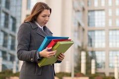 Femme d'affaires tenant des dossiers avec des documents dehors Image stock