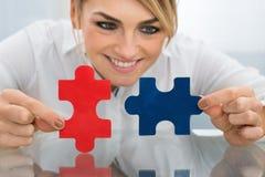 Femme d'affaires tenant des morceaux de puzzle denteux photo stock