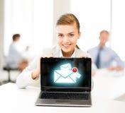 Femme d'affaires tenant l'ordinateur portable avec le signe d'email Photographie stock