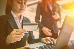 Femme d'affaires tenant la carte de crédit et à l'aide de l'ordinateur portable Sur Image libre de droits