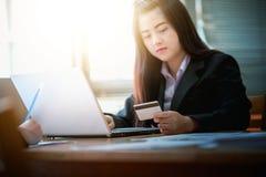 Femme d'affaires tenant la carte de crédit et à l'aide de l'ordinateur portable Sur Photo stock