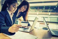 Femme d'affaires tenant la carte de crédit et à l'aide de l'ordinateur portable Sur Photos stock