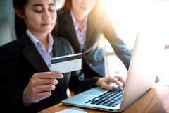 Femme d'affaires tenant la carte de crédit sur l'ordinateur portable pour des achats en ligne Images stock