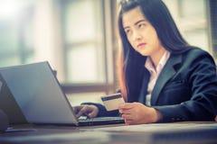 Femme d'affaires tenant la carte de crédit sur l'ordinateur portable pour des achats en ligne Photo libre de droits