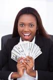 Femme d'affaires tenant la fan d'argent dans le bureau Photographie stock libre de droits