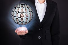 Femme d'affaires tenant le collage d'hommes d'affaires dans la sphère Photographie stock