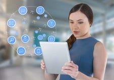 Femme d'affaires tenant le comprimé avec des icônes d'apps dans le hall lumineux de l'espace Image stock