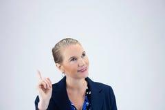 Femme d'affaires tenant le doigt droit en air regardant à gauche Photographie stock libre de droits