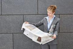 Femme d'affaires tenant le journal par temps venteux photo libre de droits