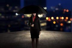Femme d'affaires tenant le parapluie se tenant sur le dessus de toit Photos libres de droits