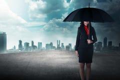 Femme d'affaires tenant le parapluie se tenant sur le dessus de toit Images libres de droits