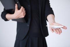 Femme d'affaires tenant le préservatif et l'essai de grossesse Photographie stock libre de droits