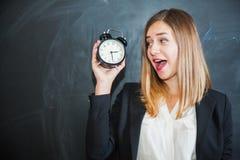 Femme d'affaires tenant le réveil avec le tableau noir sur le fond Photos libres de droits
