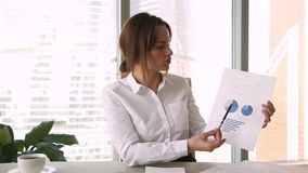 Femme d'affaires tenant le rapport financier parlant au webcam pour faire l'appel visuel clips vidéos