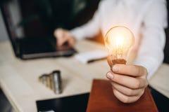 Femme d'affaires tenant les ampoules sur le bureau dans un bureau et les travaux pour l'ordinateur photographie stock