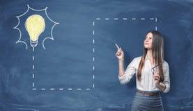 Femme d'affaires tenant son index avec venir à ligne pleine à une ampoule électrique allumée dessinée sur le mur bleu photographie stock libre de droits