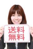 Femme d'affaires tenant une table des messages avec l'expédition gratuite d'expression dans le KANJI Photographie stock libre de droits