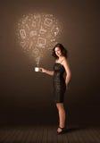Femme d'affaires tenant une tasse blanche avec les icônes sociales de media Photographie stock libre de droits