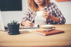 Femme d'affaires tenant une tasse de café et écrivant le plan d'action Images libres de droits