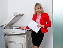 Femme d'affaires travaillant à l'imprimante de bureau Photo stock