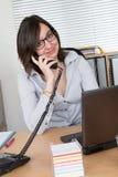 Femme d'affaires travaillant au bureau parlant à un téléphone Photo libre de droits
