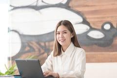 Femme d'affaires travaillant au sourire d'ordinateur portable Images stock